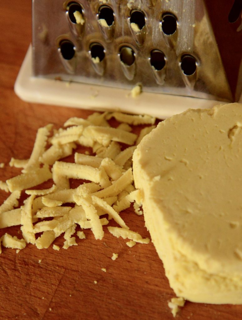 A block of plant-based cheddar cheese presented on a wooden cutting board, shown with shards of grated planted-based cheese, next to the metal grater used to grate it.