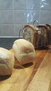 Overnight mini loaves served on a breadboard
