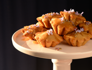 Kawakawa Tea Cakes glazed with syrup and garnished with rosemary flowers, displayed on a cake stand