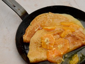 Crepe pan with crepes suzette gazed with syrup and segments of mandarins