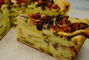 A layered potato, chickpea and caramelised onion plant-based Kuku with a wedge sliced ready to eat
